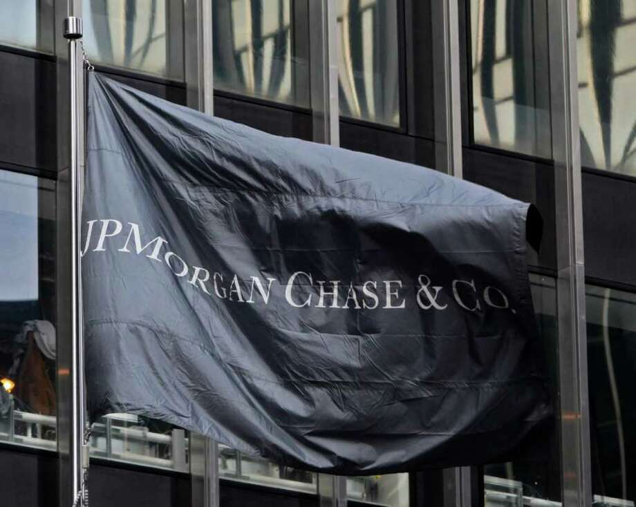 In this Feb. 4, 2011, JPMorgan Chase flag flies in front of its skyscraper building in New York.  JPMorgan Chase's first-quarter profit jumped 67 percent Wednesday, April 13, 2011, on solid growth in investment banking fees and a drop in losses in its credit card portfolio. (AP Photo/Bebeto Matthews) Photo: Bebeto Matthews