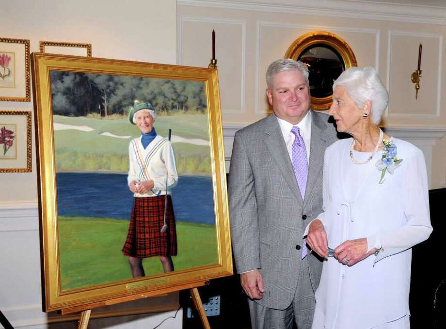 The Innis Arden Golf Club unveiled a portrait of club member and champion golfer Louise Munro, Wednesday, April 14, 2011.  Munro right, looks on with club manager Dan Farrell. Photo: Bob Luckey / Greenwich Time