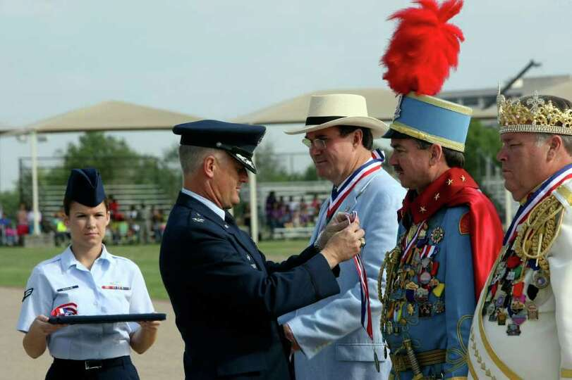 Col. William H. Mott V puts a medal on King Antonio Bill Mitchell during the Fiesta parade at Lackla