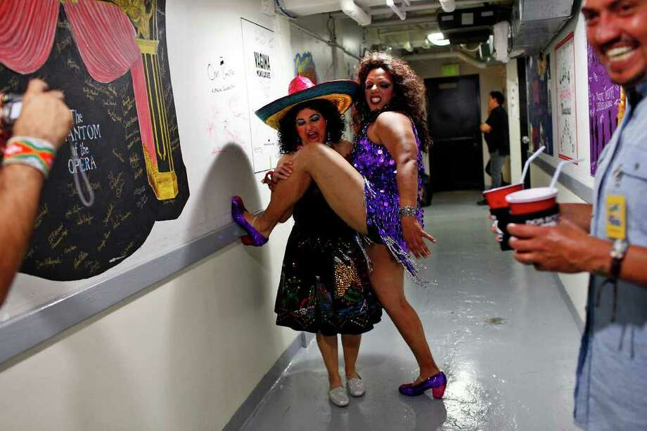 "Felice Garcia, left, of ""The Duchess of Eternal Entrepreneurial Enterprises,"" representing Oprah's Black Swan Song, left, and Andy Sanchez, of ""The Queen of Arizona ala Mode,"" play for the camera, left, backstage during Cornyation, The Court of Double-Dip Shellacking, at the Charline McCombs Empire Theatre on Tuesday, April 12, 2011. Photo: LISA KRANTZ, Lisa Krantz/Express-News / SAN ANTONIO EXPRESS-NEWS"