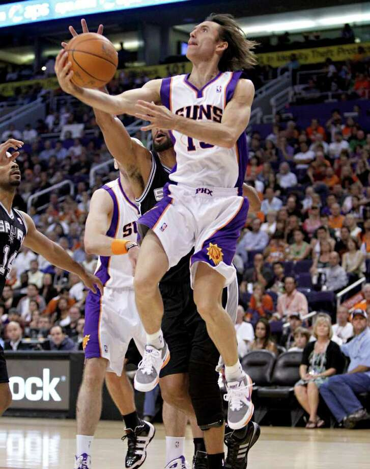 Phoenix Suns' Steve Nash drives past San Antonio Spurs' Tim Duncan, rear, during the fourth quarter of an NBA basketball game Wednesday, April 13, 2011, in Phoenix. Photo: AP
