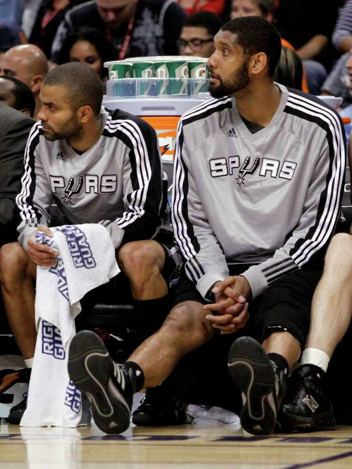 San Antonio Spurs' Tim Duncan, right, and Tony Parker, of France, watch from the bench against the Phoenix Suns' during the fourth quarter of an NBA basketball game Wednesday, April 13, 2011, in Phoenix.