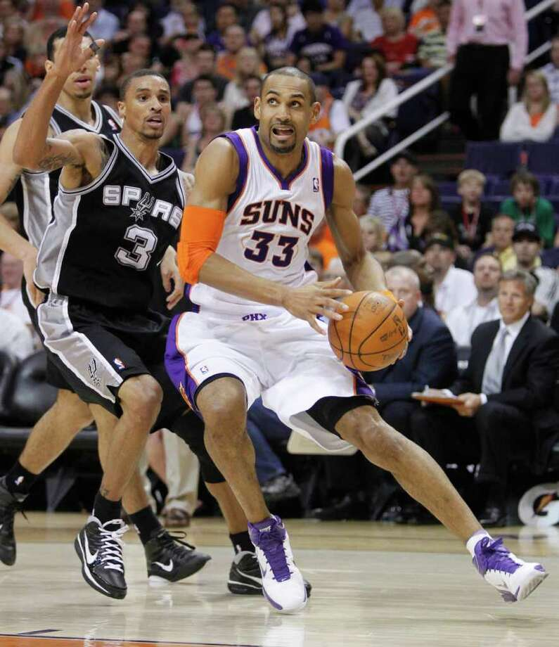 Phoenix Suns' Grant Hill (33) drives past San Antonio Spurs' George Hill (3) during the fourth quarter of an NBA basketball game Wednesday, April 13, 2011, in Phoenix. Photo: AP
