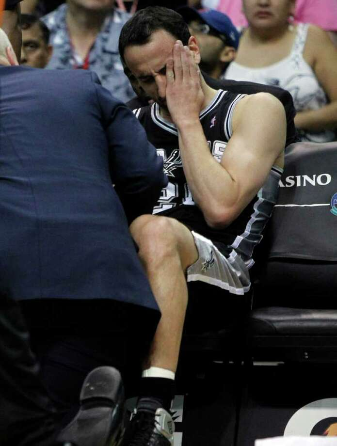San Antonio Spurs' Manu Ginobili, of Argentina, is checked by the trainer after running into Phoenix Suns' Grant Hill during the first quarter of an NBA basketball game Wednesday, April 13, 2011, in Phoenix. Ginobili had to leave the game. Photo: AP