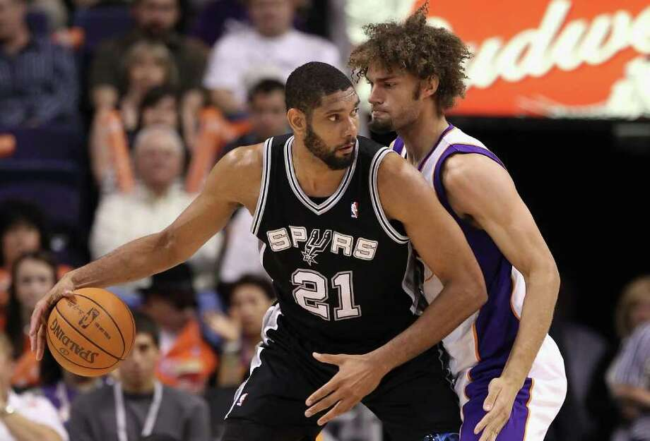 PHOENIX, AZ - APRIL 13:  Tim Duncan #21 of the San Antonio Spurs handles the ball under pressure from Robin Lopez #15 of the Phoenix Suns during the NBA game at US Airways Center on April 13, 2011 in Phoenix, Arizona.  NOTE TO USER: User expressly acknowledges and agrees that, by downloading and or using this photograph, User is consenting to the terms and conditions of the Getty Images License Agreement.  (Photo by Christian Petersen/Getty Images) *** Local Caption *** Tim Duncan;Robin Lopez Photo: Christian Petersen, Getty Images / 2011 Getty Images
