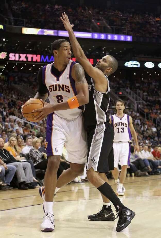 PHOENIX, AZ - APRIL 13:  Channing Frye #8 of the Phoenix Suns handles the ball under pressure from Tony Parker #9 of the San Antonio Spurs during the NBA game at US Airways Center on April 13, 2011 in Phoenix, Arizona.  NOTE TO USER: User expressly acknowledges and agrees that, by downloading and or using this photograph, User is consenting to the terms and conditions of the Getty Images License Agreement.  (Photo by Christian Petersen/Getty Images) *** Local Caption *** Channing Frye;Tony Parker Photo: Christian Petersen, Getty Images / 2011 Getty Images