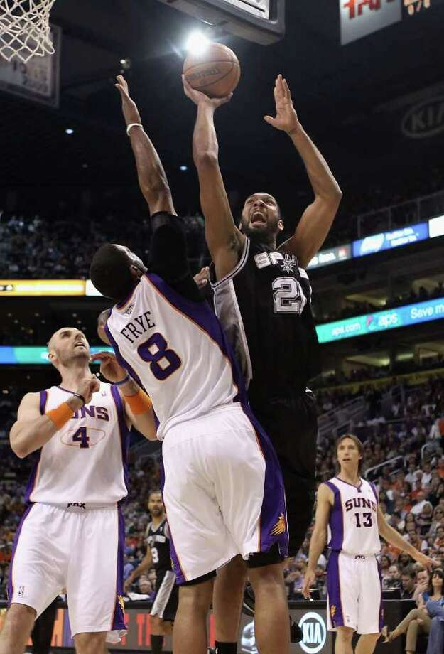 PHOENIX, AZ - APRIL 13:  Tim Duncan #21 of the San Antonio Spurs puts up a shot over Channing Frye #8 of the Phoenix Suns during the NBA game at US Airways Center on April 13, 2011 in Phoenix, Arizona.  NOTE TO USER: User expressly acknowledges and agrees that, by downloading and or using this photograph, User is consenting to the terms and conditions of the Getty Images License Agreement.  (Photo by Christian Petersen/Getty Images) *** Local Caption *** Tim Duncan;Channing Frye;Steve Nash Photo: Christian Petersen, Getty Images / 2011 Getty Images