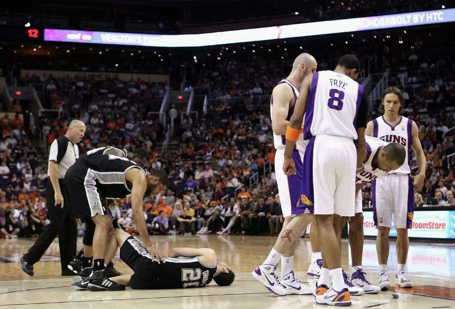 PHOENIX, AZ - APRIL 13:  Manu Ginobili #20 of the San Antonio Spurs lays on the court in pain as teammates Tim Duncan #21 and Antonio McDyess #34 lean in following a collision with Grant Hill #33 of the Phoenix Suns during the NBA game at US Airways Center on April 13, 2011 in Phoenix, Arizona.  NOTE TO USER: User expressly acknowledges and agrees that, by downloading and or using this photograph, User is consenting to the terms and conditions of the Getty Images License Agreement.  (Photo by Christian Petersen/Getty Images) *** Local Caption *** Manu Ginobili;Tim Duncan;Antonio McDyess;Antonio McDyess;Steve Nash Photo: Christian Petersen, Getty Images / 2011 Getty Images