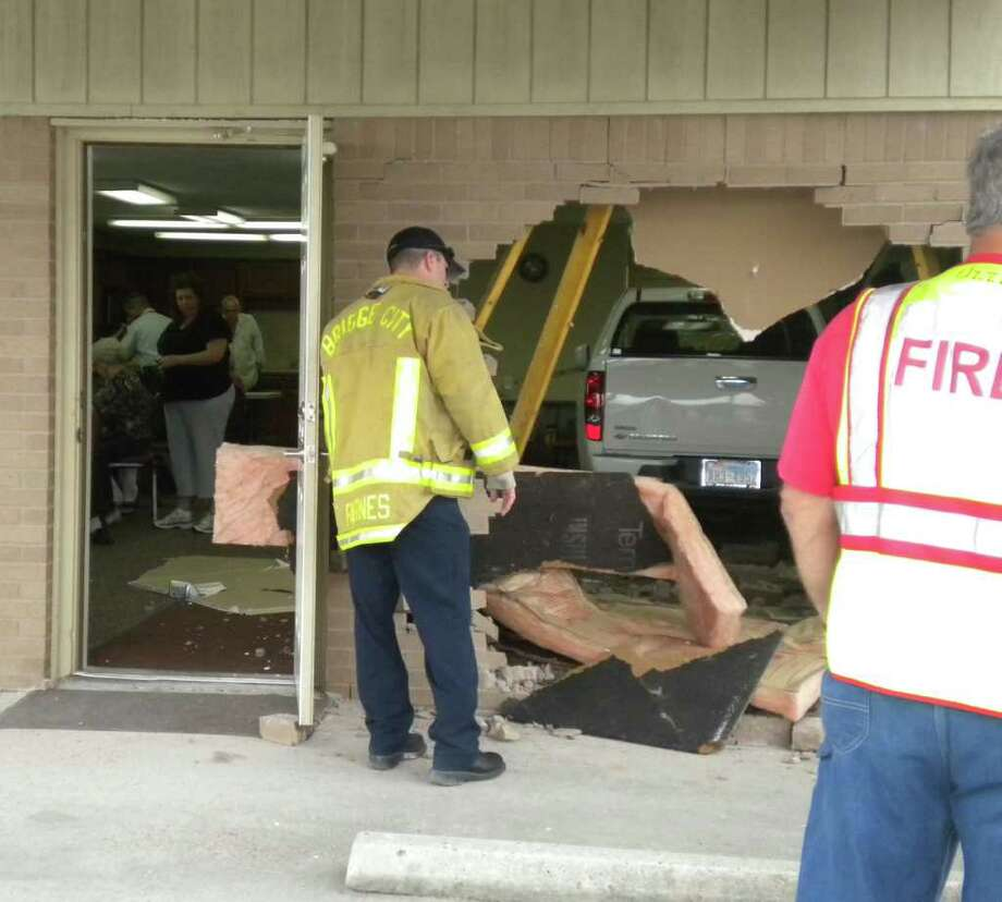 First responders try to figure out how to remove the truck that plowed through a wall and into the Bridge City Senior Citizen Center Thursday morning. The driver is said to have hit the gas instead of the brake as he pulled up to the center. No injuries were reported. Amy Moore/The Enterprise