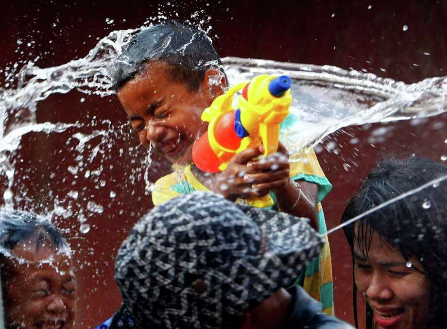 A child gets water splashed during Thai New Year celebrations in Prachinburi, east of Bangkok, Wednesday. Photo: AP