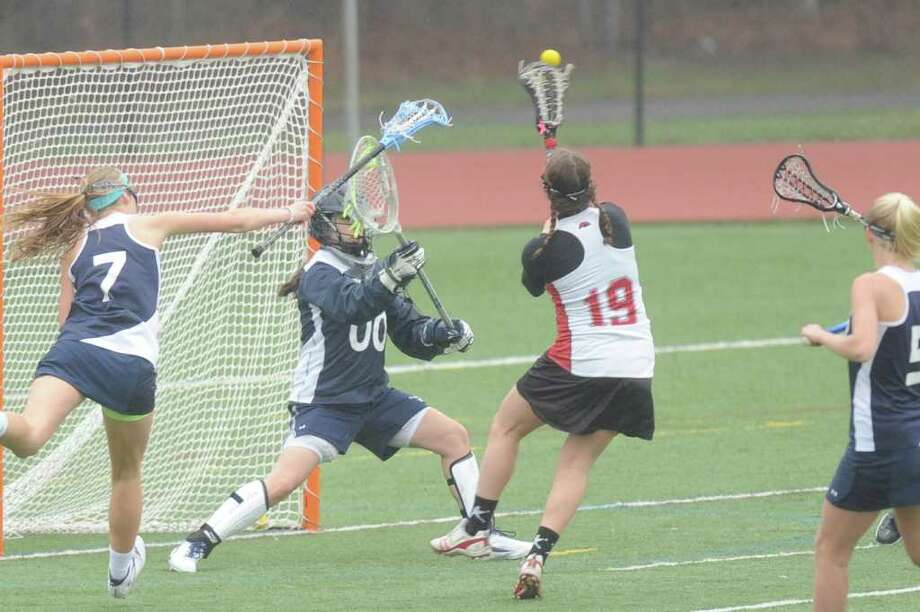 Fairfield Warde's Taylor Bargmann fires a shot past Staples' goalie Penny Tsilfides during the Mustangs' 15-9 loss to the Wreckers on Wednesday. Photo: Contributed Photo / Fairfield Citizen contributed