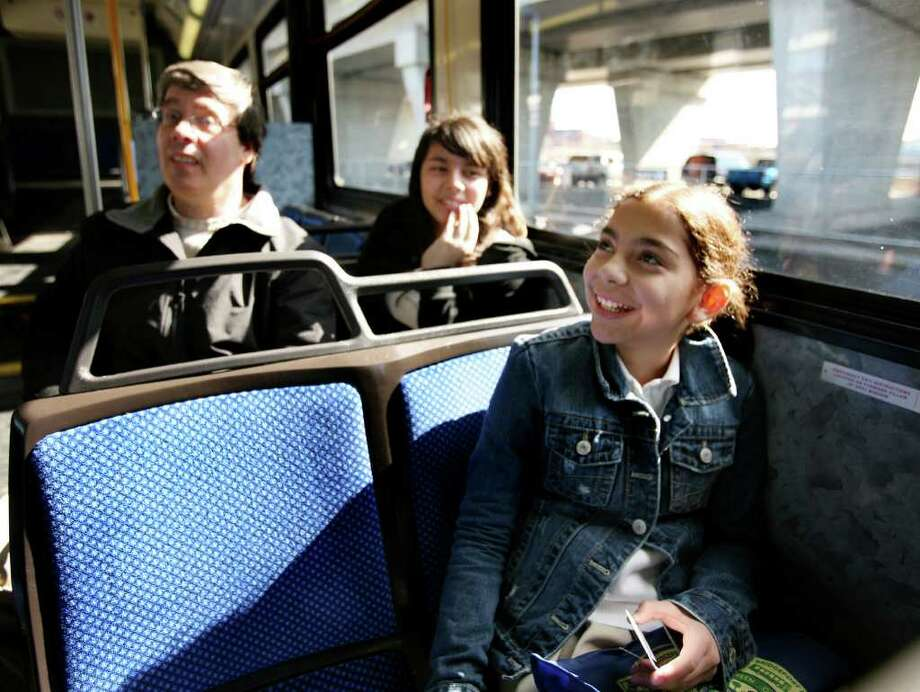 Fourth grader Rachell Perez, 11, right, smiles as she looks at her poem displayed inside a city bus in Bridgeport on Thursday, April 14, 2011. Teacher Ron Rapice, left, held a poetry contest, with winners getting their poems displayed. Seated with Rapice is another contest winner, fifth grader Alyssa Delgado, 11. Photo: Brian A. Pounds / Connecticut Post