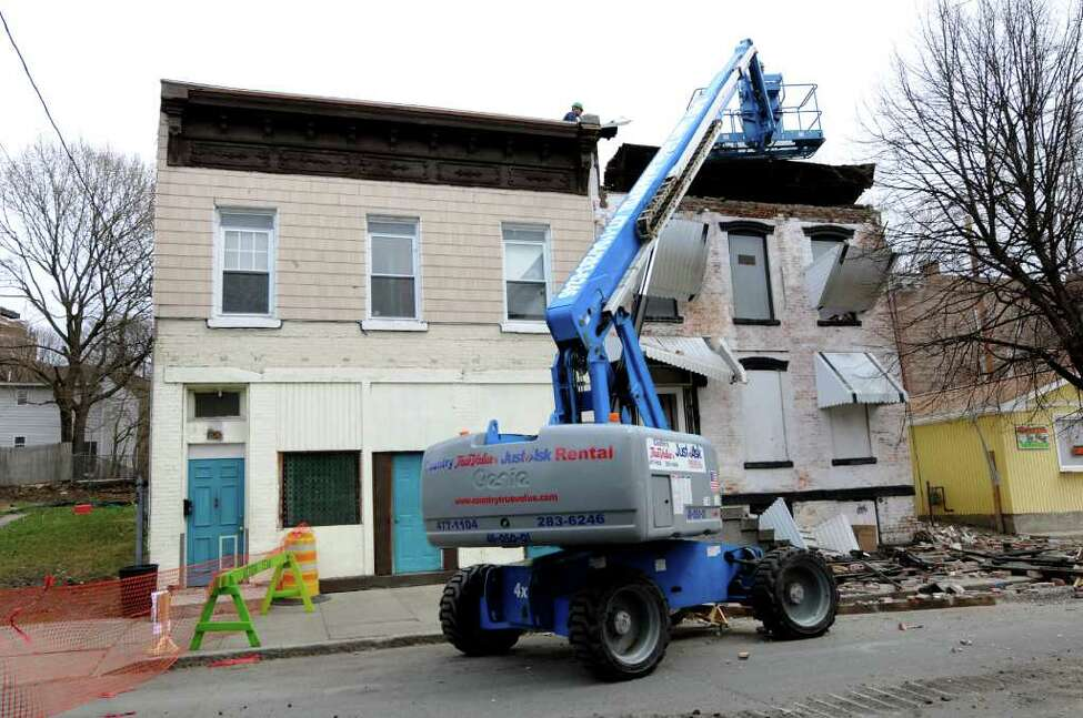 Next door to 306 9th St., left, 304 9th St., is being torn down on Tuesday, April 12, 2011, in Troy, N.Y. The two buildings share a common wall. (Cindy Schultz / Times Union)