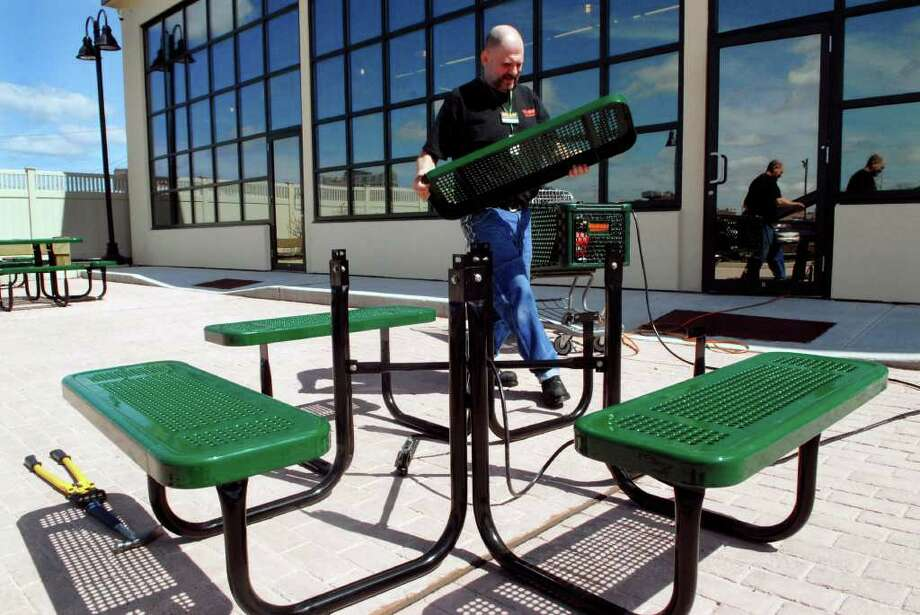 Fairway employee Kevin Scalise puts together outdoor seating  at the Stamford, Conn. store on Thursday April 14, 2011, he is one of the people hired as part of a program with St. Luke's that seeks to help clients who have struggled with joblessness and homelessness. Photo: Dru Nadler / Stamford Advocate Freelance