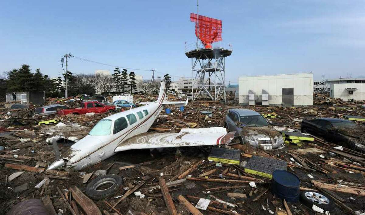 A private plane washed inshore by the tsunami sits in water and debris next to cars outside Sendai Airport in Natori, Miyagi prefecture on March 13, 2011 two days after a massive 8.9 magnitude earthquake and tsunami hit the region.