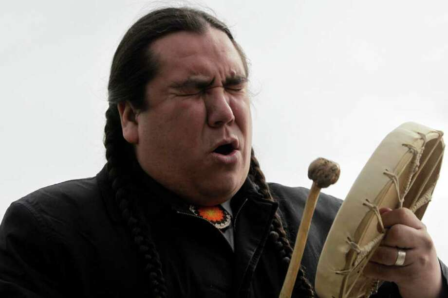 Clayton Thomas Mullen from the Indigenous Environmental Network in Canada, sings a traditional song during a protest against BP outside the conference center where BP held its annual general meeting of its shareholders, in London, Thursday, April 14, 2011. BP's annual shareholder meeting got off to a rowdy start on Thursday as crowds of protesters watched over by police held noisy demonstrations outside the venue. Photo: Lefteris Pitarakis, AP / AP