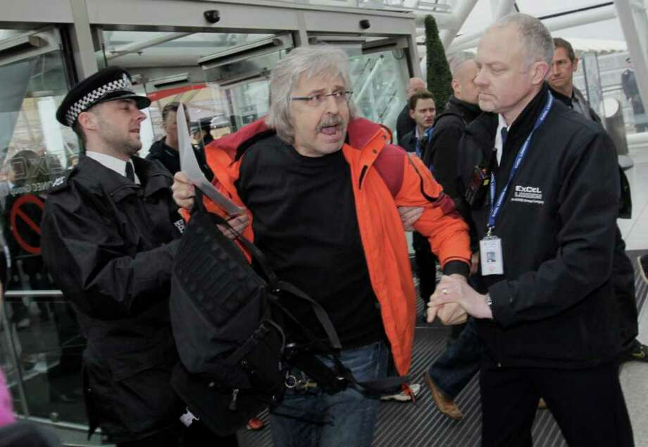 A British police officer, left, and a security guard, apprehend Axel Kohler-Schnura, of Germany, as he tries to enter the conference center where BP held its annual general meeting of its shareholders, in London, Thursday, April 14, 2011. Kohler-Schnura, was later released. BP's annual shareholder meeting got off to a rowdy start on Thursday as crowds of protesters watched over by police held noisy demonstrations outside the venue. Photo: Lefteris Pitarakis, AP / AP