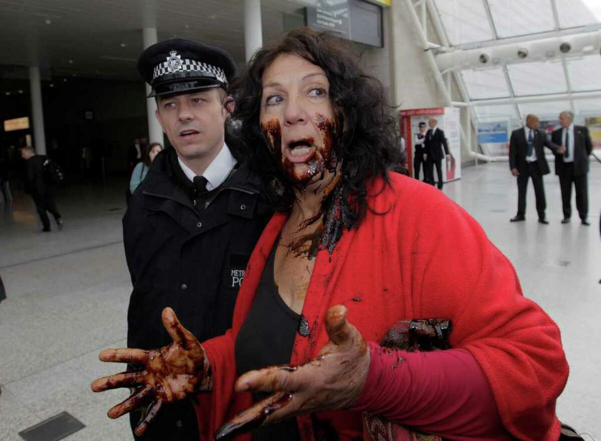 American Diane Wilson, from Texas, covered in oil, protests against BP as British police officers block her from entering the conference center where BP held its annual general meeting of its shareholders, in London, Thursday, April 14, 2011. BP's annual shareholder meeting got off to a rowdy start on Thursday as crowds of protesters watched over by police held noisy demonstrations outside the venue.