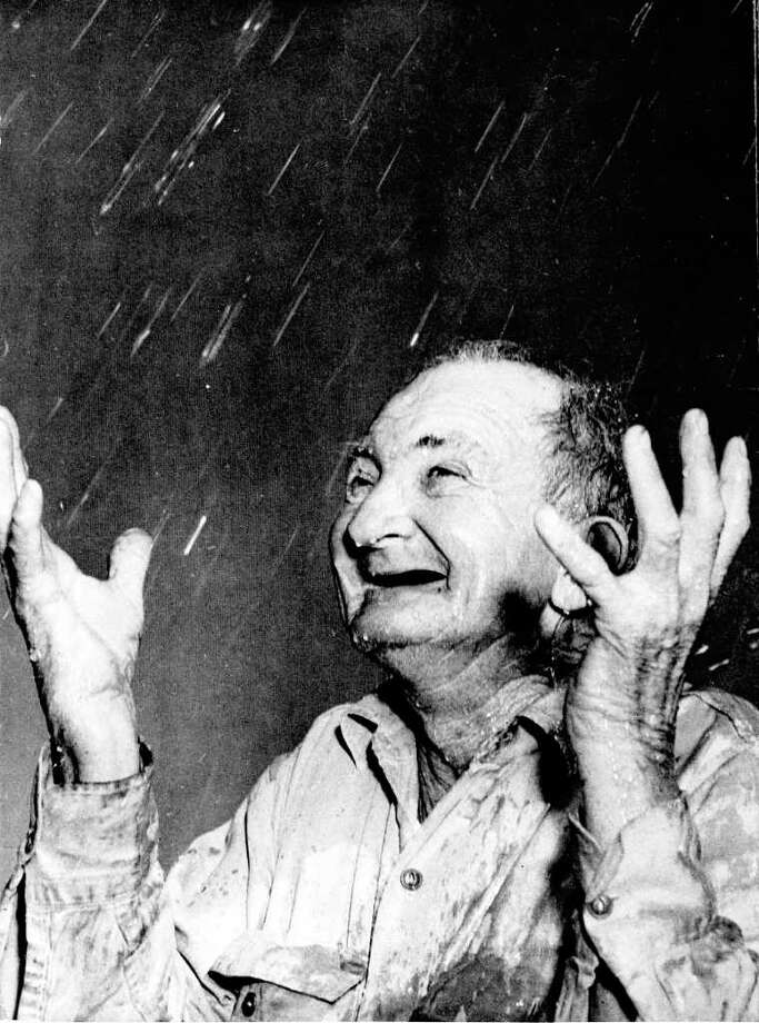 San Antonio farmer Sam Smith celebrates  rain on Easter in 1951, after a severe drought. A reader suggests S.A. go to water restrictions year-round. Photo: Harvey H. Belgin/Special To The Express-News / HARVEY H. BELGIN