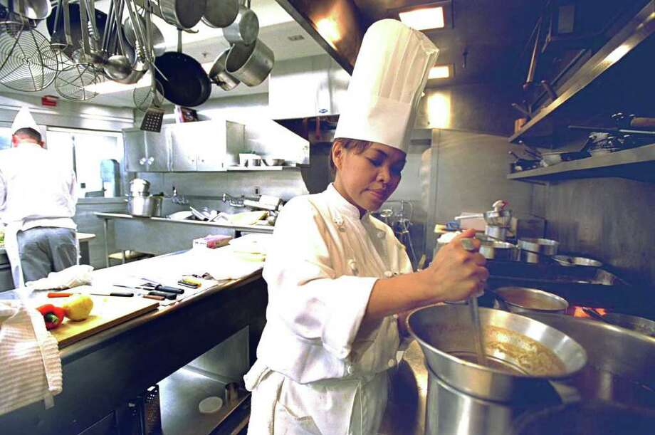 Chef Cristeta Comerford prepares a meal inside the White House kitchen. Named as White House executive chef by President George W. Bush, Comerford has been retained by the Obamas. Photo: TINA HAGER, The White House / THE WHITE HOUSE