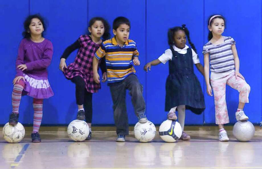 Soccer stars from left, Kenia Rossil, Michaela Tzul, Anthony Pena, Nova Moore-Ramseur and Sabrina Castana listen as professional soccer player Keith Donahue teaches them how to hone their ball skills at the Chester Addison Community Center in Stamford, Conn., April 14, 2011. Donahue took off from San Diego in February on a 50-state tour performing one volunteer act in each state during his trek. For his Connecticut stop he chose to help DOMUS for the day. After spending the morning shelving books and reading to kids he ran a soccer workshop for the students for the afternoon. Photo: Keelin Daly / Stamford Advocate