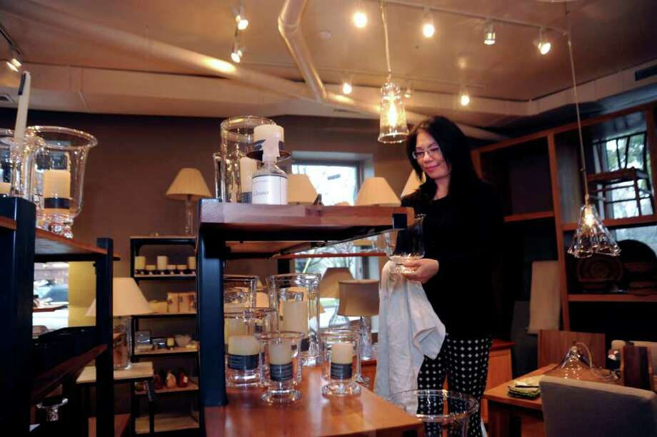 Sales associate Mildren Yuen polishes glass at Simon Pearce's new store on 125 East Putnam Ave., at Greenwich, on Wednesday, April 13, 2011. The store will be open on Friday, April 15, 2011. Photo: Helen Neafsey / Greenwich Time