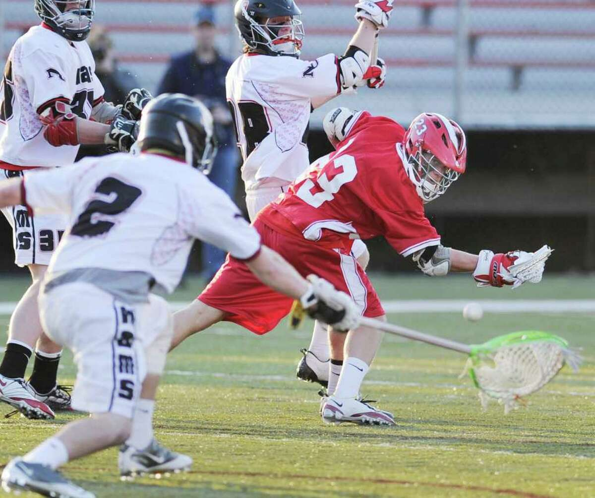 Alex Marcus trys a backhand shot that is blocked by New Canaan goalie Jimmy Joe Granito, # 2, left, during boys lacrosse game between Greenwich High School and New Canaan High School at New Canaan High School, Thursday afternoon, April 14, 2011.