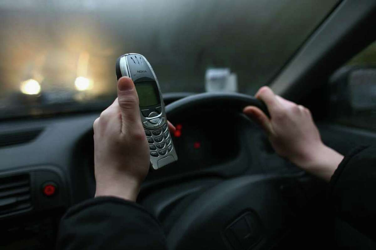 GLASGOW, UNITED KINGDOM - FEBRUARY 27: In this photo illustration a woman uses her mobile phone February 27, 2007 in Glasgow, Scotland. Drivers who use hand-held mobile phones while driving will now face fixed penalty fine of GBP60 and three penalty points on their driving licence. (Photo by Jeff J Mitchell/Getty Images)
