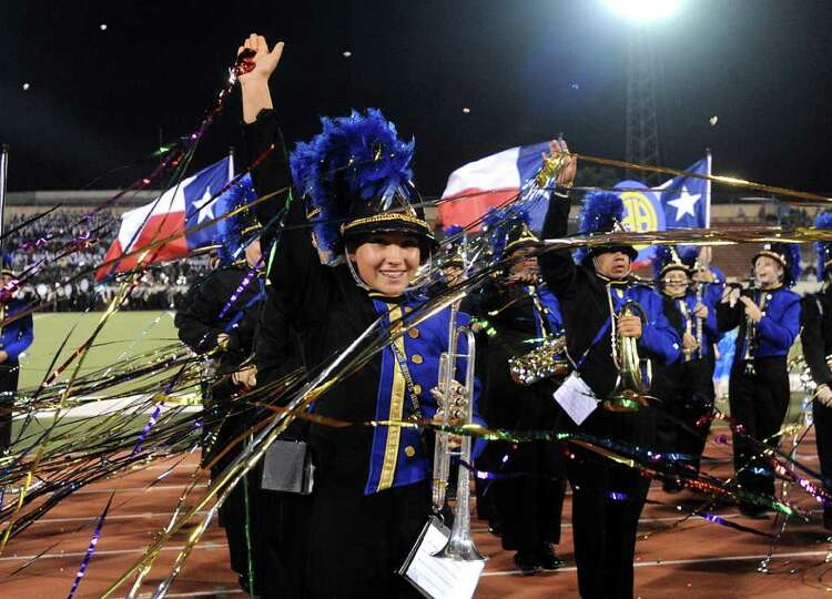 Members of the Alamo Heights High School Band throw streamers during the 73rd Battle of Flowers Band