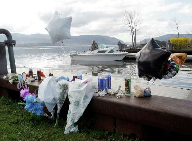 A fisherman is seen behind an informal memorial at the boat ramp where Lashanda Armstrong drove her minivan into the Hudson River on Tuesday night killing herself and three of her children, in Newburgh, N.Y., on Thursday, April 14, 2011. (AP Photo/Mike Groll) Photo: Mike Groll