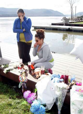 Natasha Colon, left, and Nicole Callahan, both of Newburgh, N.Y., visit a memorial at the boat ramp where Lashanda Armstrong drove her minivan into the Hudson River on Tuesday night killing herself and three of her children, in Newburgh, on Thursday, April 14, 2011. (AP Photo/Mike Groll) Photo: Mike Groll