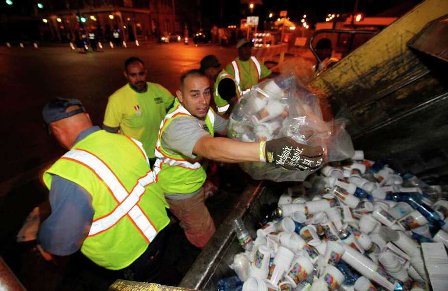 Lupe Nuñez (center) joins other city workers as they toss plastic cups and aluminum bottles into the back of a compactor truck after the first opening night of NIOSA at La Villita on Tuesday, April 12, 2011. The event is one of the Fiesta Commission's testing grounds for green initiatives, and the Conservation Society and the city are stepping up efforts to recycle party debris. Photo: KIN MAN HUI, Kin Man Hui/Express-News / San Antonio Express-News