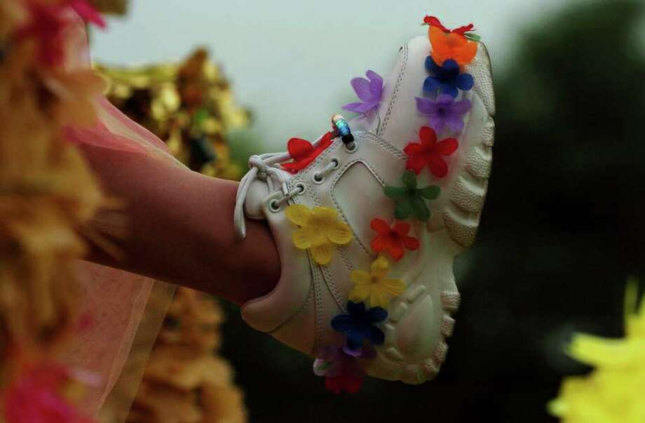 A rider on the Miss Fiesta float shows her shoes during the Fiesta Battle of Flowers Parade Friday, April 20, 2004.NICOLE FRUGE/SAN ANTONIO EXPRESS-NEWS Photo: Nicole Fruge, San Antonio Express News / San Antonio Express News