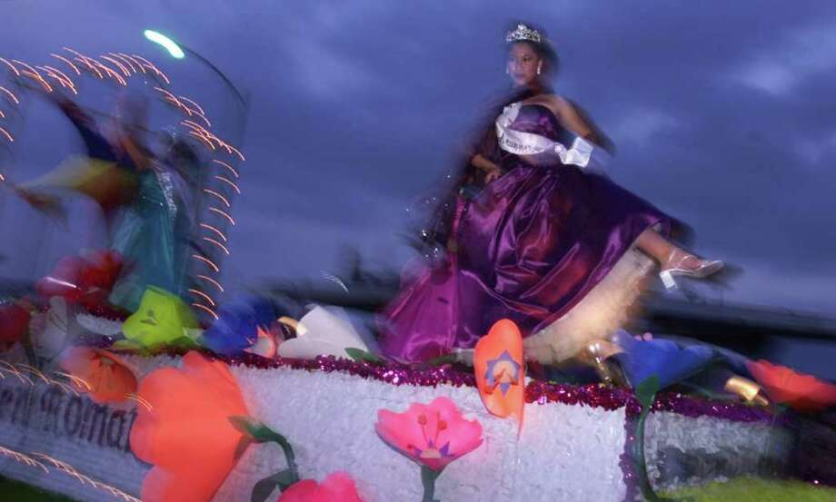 A rider aboard the Miss Fiesta San Antonio float shows the crowd her shoes as the float makes its way down Broadway. PHOTO BY EDWARD A. ORNELAS Photo: Edward A. Ornelas