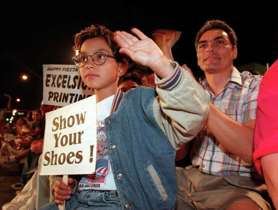 "METRO - Mark Anthony L. Araiza, 7, holds the traditional ""Show Your Shoes"" sign to encourage the parade queens at the Fiesta Flambeau Parade on Saturday night. 4-25-98. Kin Man Hui/staff. Photo: KIN MAN HUI"