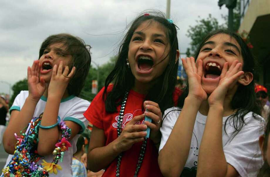 "METRO - 2:42 PM: Miranda Suarez, left, and sisters Brianna and Miranda Aguirre yell ""Show me your shoes!"" to a duchess during the Fiesta Battle of Flowers Parade Friday, April 28, 2006. BAHRAM MARK SOBHANI/STAFF Photo: BAHRAM MARK SOBHANI, SAN ANTONIO EXPRESS NEWS / SAN ANTONIO EXPRESS NEWS"