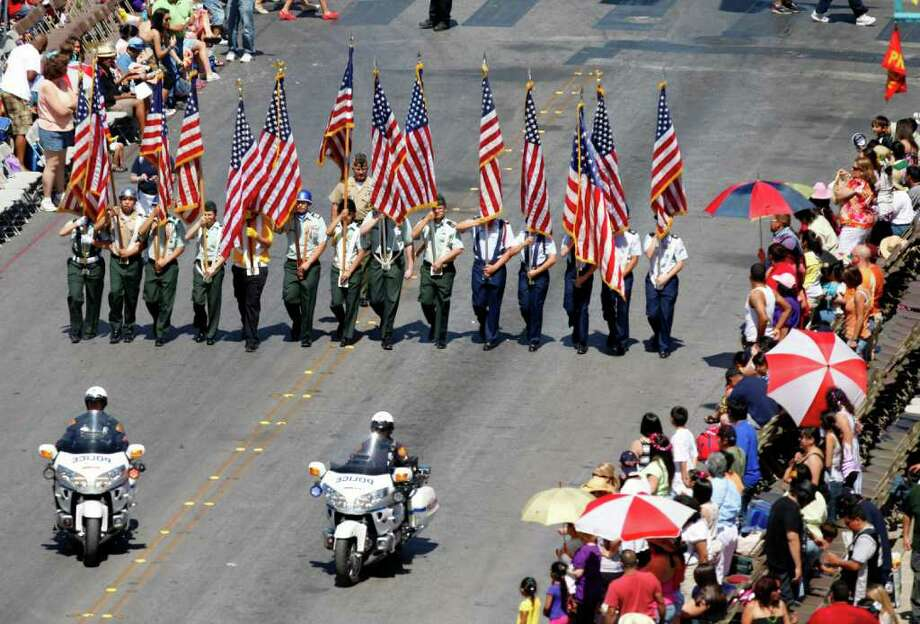 The first color guard makes its way along the route during the Battle of Flowers parade April 15, 2011 in downtown San Antonio. Photo: WILLIAM LUTHER, Wluther@express-news.net / © 2011 San Antonio Express-News