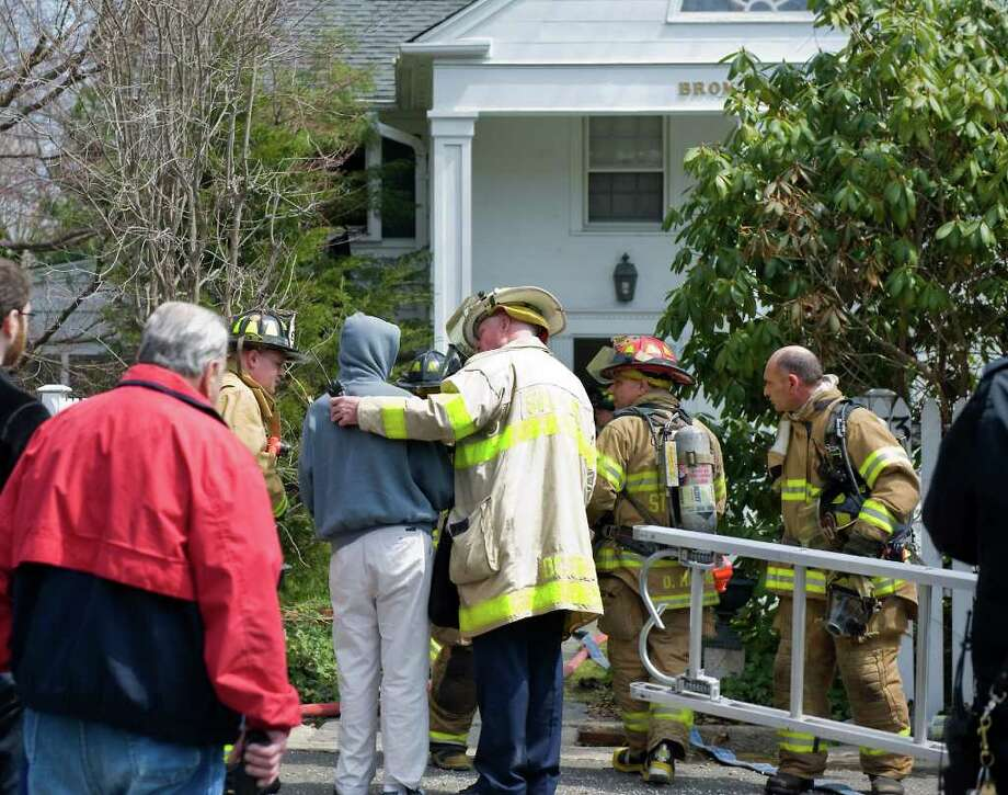 Deputy Chief Tim Conroy consoles the owner of the home as Stamford firefighters respond to a fire on Hoyclo Road in Stamford, Conn. on Friday April 15, 2011. Photo: Kathleen O'Rourke / Stamford Advocate