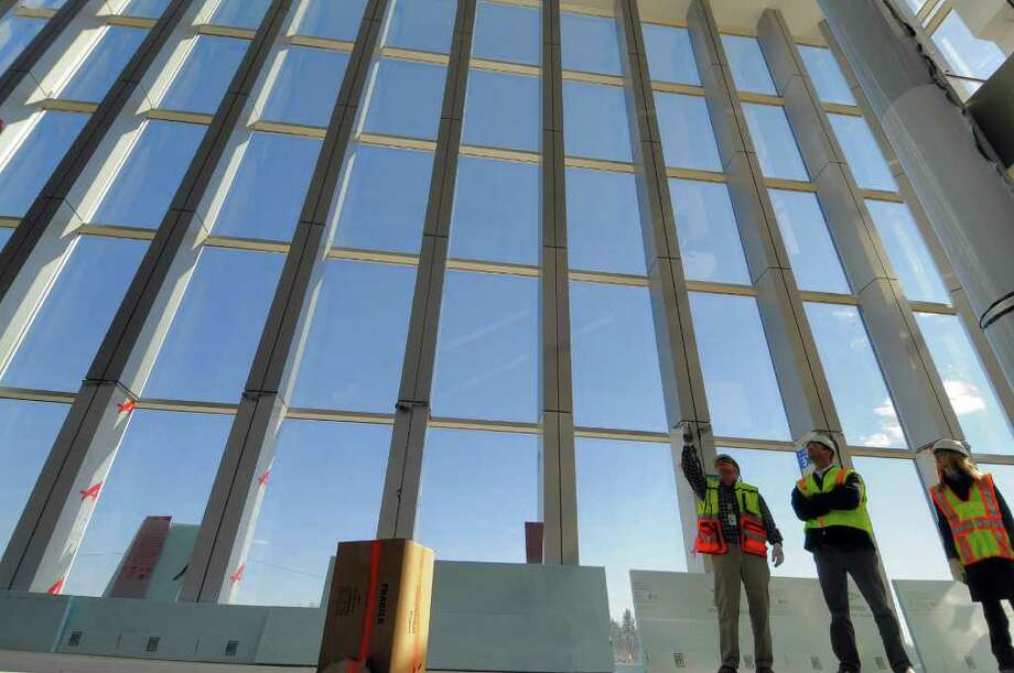 Allen Cullion, General Superintendent for M + W Group, left, Travis Bullard, center, and Jessica Shahda, right, both of GlobalFoundries, stand inside part of the administration building of the new GlobalFoundries chip fabrication plant under construction on Thursday April 7, 2011 in Malta, NY. A giant logo of GlobalFoundries will be on a wall facing the windows behind them. (Philip Kamrass/ Times Union ) Photo: Philip Kamrass
