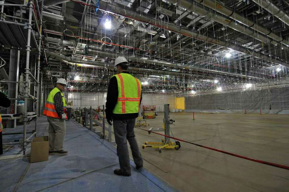Allen Cullion, General Superintendent for M + W Group, left, and Travis Bullard, right,  of GlobalFoundries, walk through part of a partially completed clean room of the new GlobalFoundries chip fabrication plant under construction on Thursday April 7, 2011 in Malta, NY. Beyond the curtained wall at far right is another part of the clean room in a more advanced state, but photographs were not allowed. (Philip Kamrass/ Times Union ) Photo: Philip Kamrass