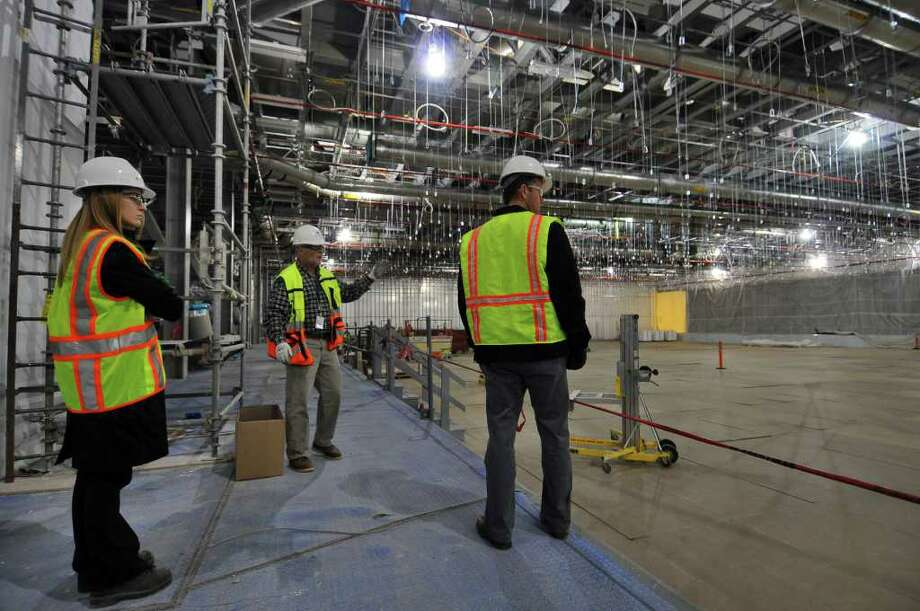Allen Cullion, General Superintendent for M + W Group, center, Travis Bullard, right, and Jessica Shahda of GlobalFoundries, left, walk through part of a partially completed clean room of the new GlobalFoundries chip fabrication plant under construction on Thursday April 7, 2011 in Malta, NY. Beyond the curtained wall at far right is another part of the clean room in a more advanced state of completion, but photographs were not allowed. (Philip Kamrass/ Times Union ) Photo: Philip Kamrass