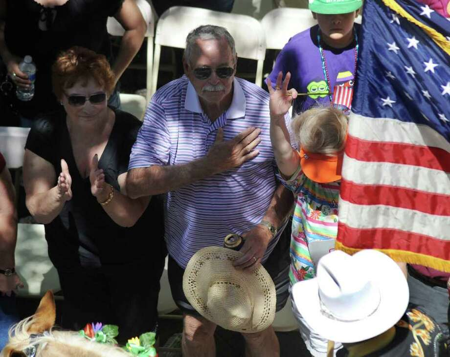 People at the Battle of Flowers Parade pay their respects as the Stars and Stripes approach on Friday, April 15, 2011. BILLY CALZADA / gcalzada@express-news.net Photo: BILLY CALZADA, SAN ANTONIO EXPRESS-NEWS / gcalzada@express-news.net