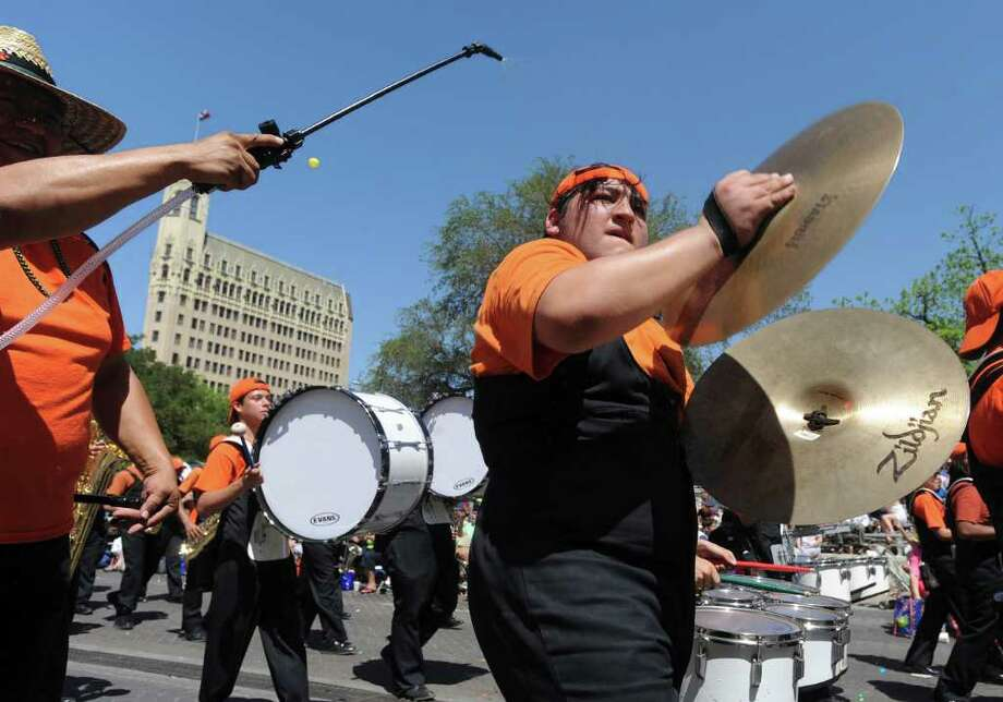 Paulo Aguilera helps Burbank cymbal player Alexander Segovia cool downduring the Battle of Flowers Parade on Friday, April 15, 2011. BILLY CALZADA / gcalzada@express-news.net Photo: BILLY CALZADA, SAN ANTONIO EXPRESS-NEWS / gcalzada@express-news.net