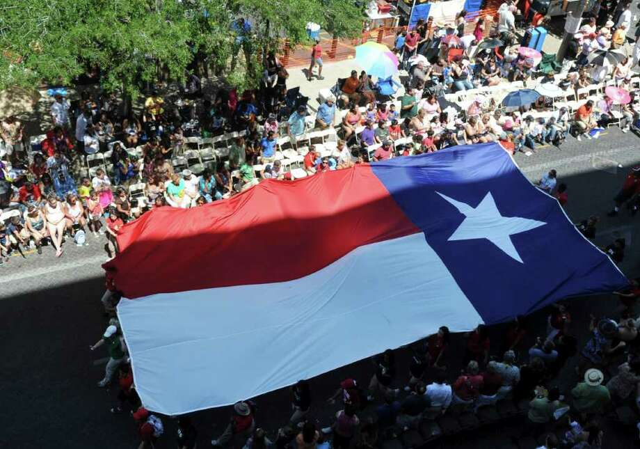 The flag of Texas is carried along East Commerce during the Battle of Flowers Parade on Friday, April 15, 2011. BILLY CALZADA / gcalzada@express-news.net Photo: BILLY CALZADA, SAN ANTONIO EXPRESS-NEWS / gcalzada@express-news.net