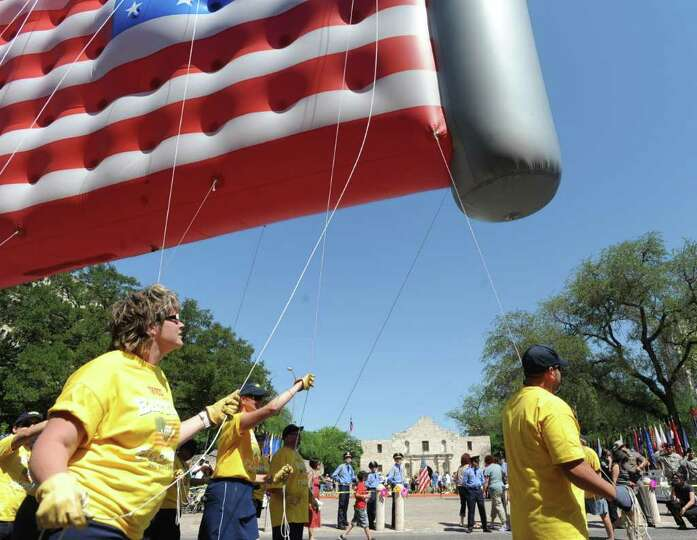 Tetco employees hold on to a flag balloon by the Alamo Shrinie during the Battle of Flowers Parade o