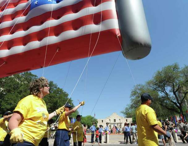 Tetco employees hold on to a flag balloon by the Alamo Shrinie during the Battle of Flowers Parade on Friday, April 15, 2011. BILLY CALZADA / gcalzada@express-news.net Photo: BILLY CALZADA, SAN ANTONIO EXPRESS-NEWS / gcalzada@express-news.net