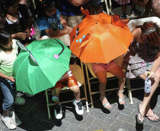 Children shelter themselves from the sun as they watch the Battle of Flowers Parade on Friday, April