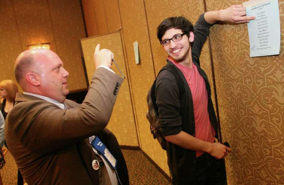 Tyler Junior College, Texas student Joshua Eguia, right, has his picture taken by his coach, Daren Carpenter, Friday afternoon, April 15, 2011, at the Hyatt Regency Greenwich after finding out he has moved into the gold round in Prose Interpretation of the 2011 Phi Rho Pi National Speech and Debate Tournament. Photo: David Ames, David Ames/For Greenwich Time / Greenwich Time Freelance