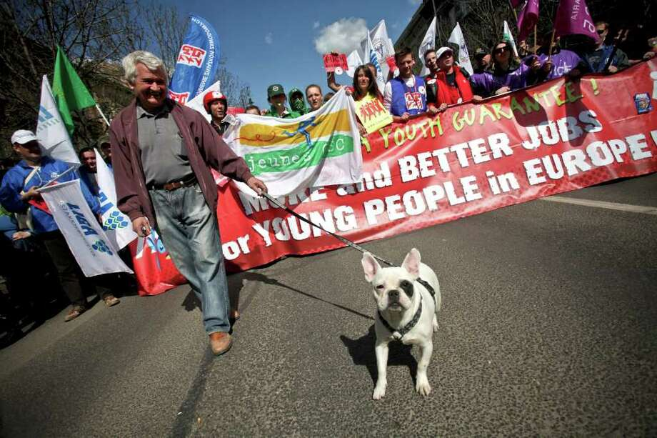 A local owner walks with his dog as activists of several national trade unions and the European Trade Union Confederation march with their banners and flags in Budapest, Hungary on April 9, 2011. European and local trade unions held a massive demonstration to protest austerity measures, which European finance ministers said were unavoidable. Photo: AFP/Getty Images