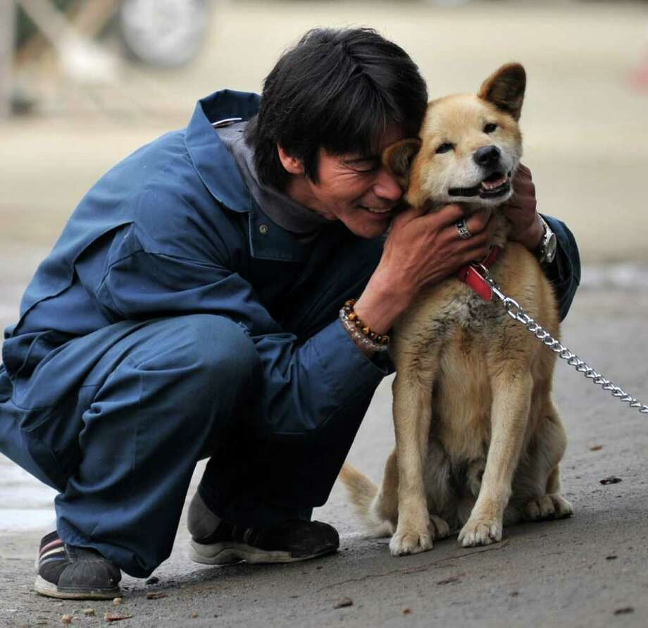 An evacuee nestles with a dog at a shelter in Rikuzentakata, Iwate prefecture, Japan on April 9, 2011.  Three dozen households in this remote coastal town became the first to move into temporary homes, nearly a month after a massive tsunami barreled into Japan. Photo: AFP/Getty Images